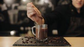 Barman transformant le chocolat chaud verser à partir d'une cuillère en tasse en verre Plan rapproch? clips vidéos