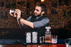 Barman using shaker and bartending tools for preparing cocktails stock image
