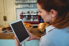 Barman utilisant la tablette au café image libre de droits
