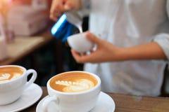 Barman utilisant le broc pour le lait se renversant dans la tasse de latte de café photographie stock