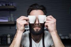 Barman utrzymuje filiżanki kawy blisko stawiać czoło; Obrazy Royalty Free