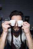 Barman utrzymuje filiżanki kawy blisko stawiać czoło; Zdjęcia Stock