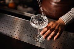 Barman versant dans le verre de champagne et faisant sensation Photographie stock libre de droits