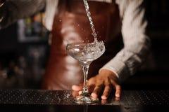 Barman versant dans le verre de champagne et faisant sensation Photos stock