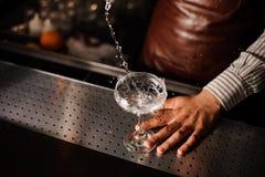 Barman versant dans le verre de champagne et faisant sensation Image libre de droits