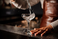 Barman versant dans le verre de champagne et faisant sensation Photos libres de droits