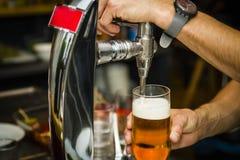 Barman versant la bière froide fraîche du robinet photographie stock libre de droits