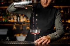 Barman versant la boisson alcoolisée avec campari dans le verre de cocktail image stock