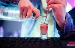 Barman versant la boisson alcoolisée dans des verres photo stock