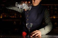 Barman versant la boisson alcoolisée dans le verre images libres de droits