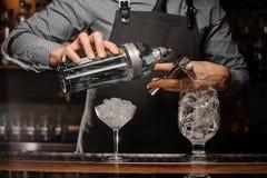 Barman versant la boisson alcoolisée dans un verre utilisant une petite mesure pour préparer un cocktail Images libres de droits