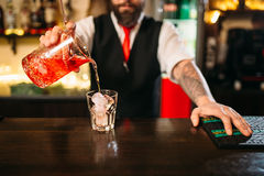 Barman versant la boisson alcoolisée en verre Photos stock