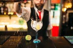 Barman versant la boisson alcoolisée en verre Photographie stock libre de droits