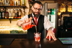 Barman versant la boisson alcoolisée en verre Photos libres de droits