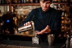 Barman versant un cocktail alcoolique dans un verre d'un dispositif trembleur en acier Images libres de droits