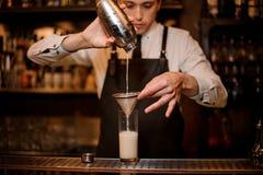Barman versant une boisson alcoolisée du dispositif trembleur en acier Photographie stock libre de droits
