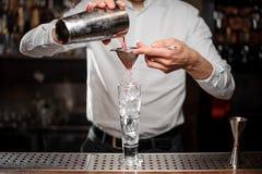 Barman versant une boisson alcoolisée du dispositif trembleur en acier Photographie stock