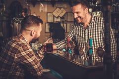 Barman versant une pinte de bière au client dans un bar Photographie stock libre de droits