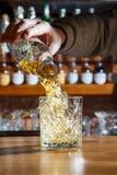 Barman w barze nalewa alkoholicznego koktajl w szkło z potężnym strumieniem, przestraszonym rozlewać na stole Zdjęcia Stock