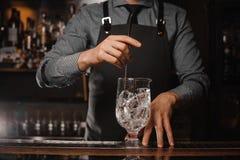 Barman w fartuch porywających kostkach lodu z pomocą łyżka zdjęcia stock
