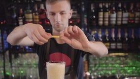 Barman w restauracji przy barem robi wyśmienicie koktajlowi i słuzyć szkło z kawałkiem cytryna zbiory
