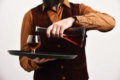 Barman w rocznika zamszowy rzemienny kamizelkowym nalewa scotch lub brandy zdjęcie stock