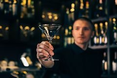 Barman watches a crystal glass. The bartender cleaning the glass on the bar stock photos