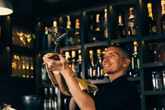 Barman watches a crystal glass. The bartender cleaning the glass on the bar stock photo