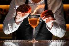 Barman making a fresh alcoholic drink with a smoky note. Barman in white shirt making a fresh alcoholic drink with smoky note on the bar counter Stock Images