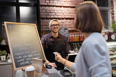 Barman and woman paying with credit card at cafe Stock Photo