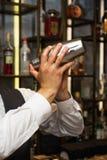 Barman at work, preparing cocktails. Shaking cocktail shaker. Stock Photo
