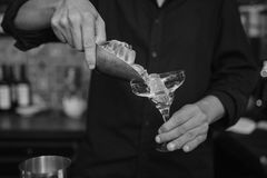 Barman at work in the pub. Making cocktails. Black and white photo stock photography