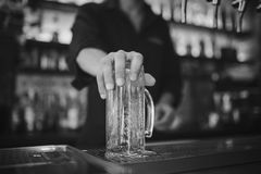 Barman at work in the pub. Washing the glass. Black and white photo. Close up on glass stock photo