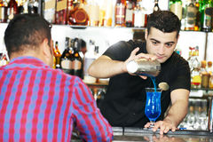 Barman worker serving cocktail in bar royalty free stock photography