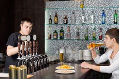 Barman working while a customer drinks at the pub stock images