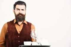 Barman z dumnymi twarz serw herbata lub alkoholu napojem Kelner z białą herbacianą filiżanką, garnkiem i szkłami na tacy, obrazy royalty free