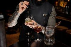 Barman z tatuażem robi świeżemu i słodkiemu lato koktajlowi z wiśniami obrazy stock