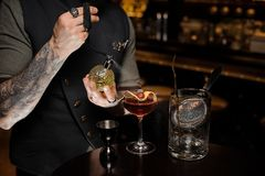Barman z tatuażem robi świeżemu, słodkiemu lato koktajlowi z i obraz royalty free