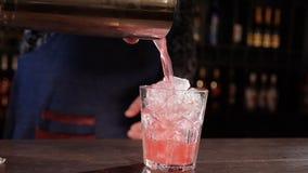 Barmanhanden die de mengeling van een schudbekerkop gieten - langzame motie stock videobeelden
