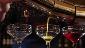 Barmanhanden die drie gekleurde cocktails gieten gelijktijdig - sluit omhoog stock videobeelden