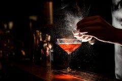 Barmans übergibt das Besprühen des Safts in das Cocktailglas stockbild