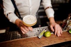 Barmans händer med coctail på stången står royaltyfri foto