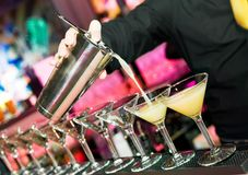 Barmans hand with shaker. Barman hand with shake mixer pouring cocktail into glasses arranged in a line stock photography