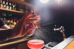 Barmans handen die het sap bestrooien die in het cocktailglas met alcoholische drank op de donkere achtergrond wordt gevuld stock foto