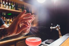 Barmans handen die het sap bestrooien die in het cocktailglas met alcoholische drank op de donkere achtergrond wordt gevuld royalty-vrije stock foto's