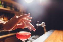 Barmans handen die het sap bestrooien die in het cocktailglas met alcoholische drank op de donkere achtergrond wordt gevuld stock afbeelding