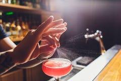 Barmans handen die het sap bestrooien die in het cocktailglas met alcoholische drank op de donkere achtergrond wordt gevuld stock foto's
