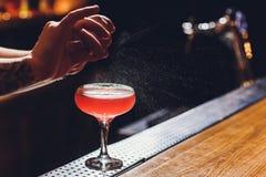 Barmans handen die het sap bestrooien die in het cocktailglas met alcoholische drank op de donkere achtergrond wordt gevuld royalty-vrije stock afbeeldingen