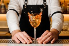 Barmans hands holding a glass with splashing alcoholic drink Royalty Free Stock Photography