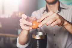 Barmans hands making cocktail with egg yolk Stock Image